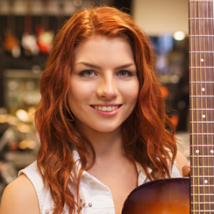 photodune-10057498-assistant-or-customer-with-guitar-at-music-store-s